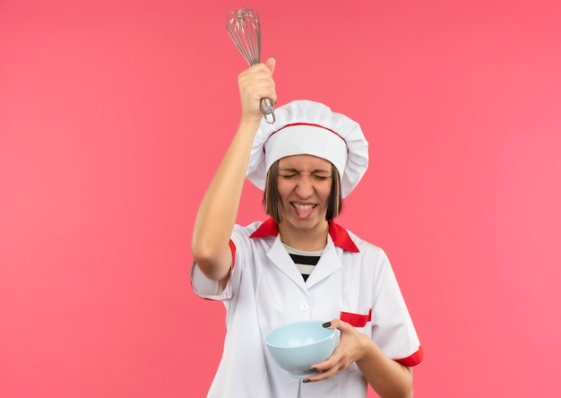 Игривая молодая женщина-повар в униформе шеф-повара держит миску и поднимает венчик над головой и показывает язык с закрытыми глазами, изолированными на розовом фоне с копией пространства