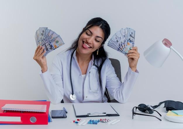 고립 된 닫힌 눈으로 혀를 보여주는 돈을 들고 의료 도구와 책상에 앉아 의료 가운과 청진기를 입고 장난 젊은 여성 의사