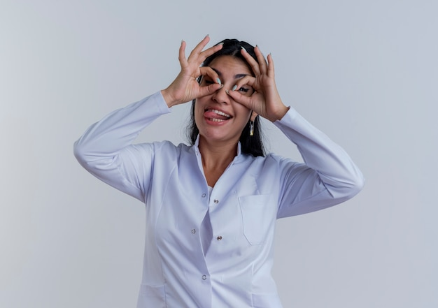 孤立したように見えるジェスチャーをしている舌を示す医療ローブを身に着けている遊び心のある若い女性医師