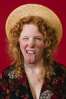 Playful young ginger woman showing tongue