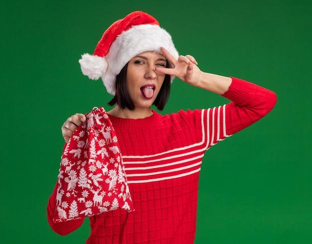 Игривая молодая девушка в шляпе санта-клауса держит рождественский подарочный мешок, показывая язык и символ v-знака возле глаза, изолированного на зеленой стене