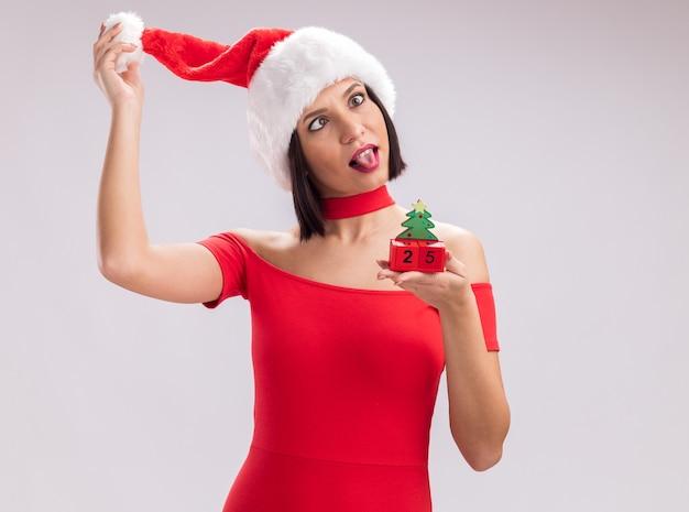 Giocosa ragazza che indossa santa hat holding albero di natale giocattolo con data grabbing hat che mostra la lingua con gli occhi incrociati isolati su sfondo bianco con spazio di copia