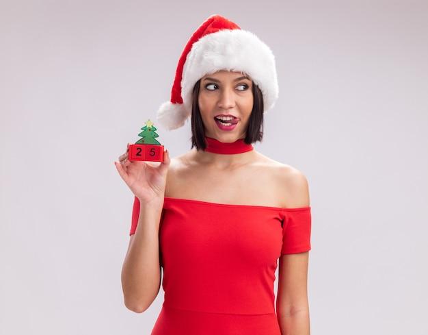 흰색 배경에 고립 된 혀를 보여주는 측면을보고 날짜와 크리스마스 트리 장난감을 들고 산타 모자를 쓰고 장난 어린 소녀