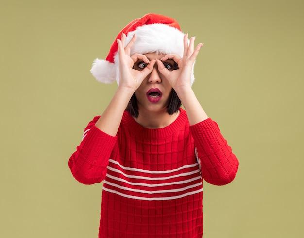 올리브 녹색 배경에 고립 된 교차 눈을 가진 쌍안경으로 손을 사용하여 제스처를보고 카메라를보고 산타 모자를 쓰고 장난 어린 소녀