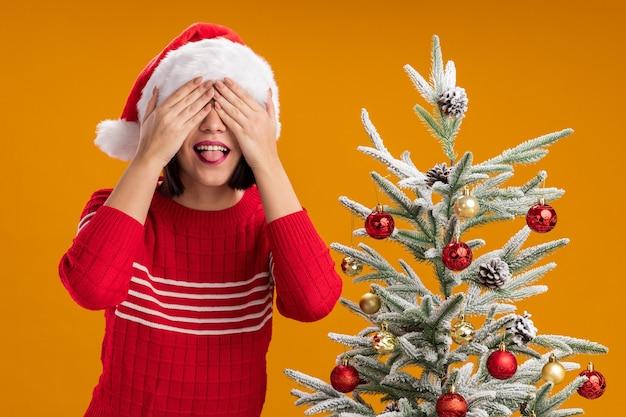 オレンジ色の壁に分離された舌を示す手で目を覆う装飾されたクリスマスツリーの近くに立っているサンタの帽子をかぶった遊び心のある若い女の子