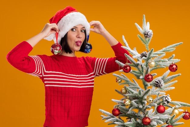 Giocosa ragazza che indossa il cappello di babbo natale in piedi vicino all'albero di natale decorato appeso palline di natale sulle orecchie guardando la telecamera che mostra la lingua isolata su sfondo arancione