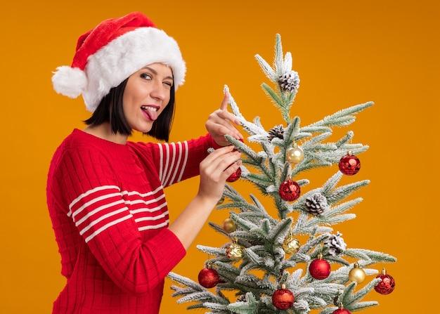 Giocoso giovane ragazza che indossa il cappello della santa in piedi in vista di profilo vicino all'albero di natale decorarlo con palline di natale guardando la telecamera che mostra la linguetta isolata su sfondo arancione