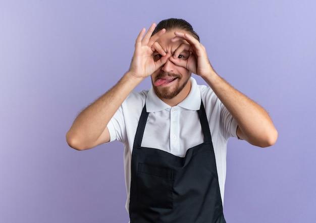 Giocosa giovane barbiere bello che indossa l'uniforme che fa il gesto di sguardo usando le mani come binocolo e mostrando la linguetta isolata su fondo viola