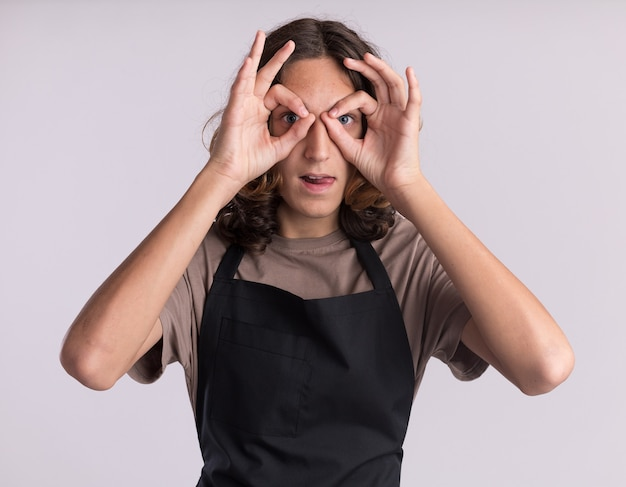 舌を示す双眼鏡として手を使って見ているジェスチャーをしている制服を着ている遊び心のある若いハンサムな理髪師