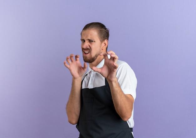 Игривый молодой красивый парикмахер в униформе делает тигровый рык и жест лап на фиолетовом фоне с копией пространства