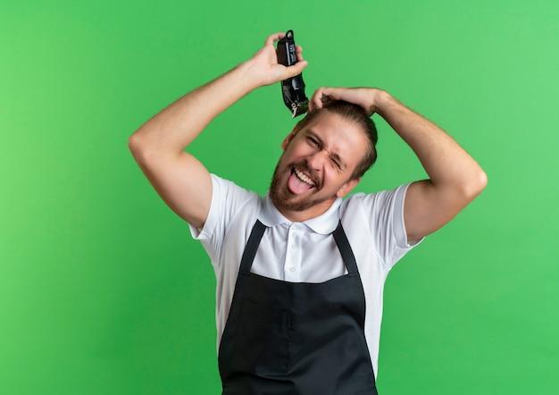 Игривый молодой красивый парикмахер в униформе, подстригающий волосы рукой на голове, подмигивая и показывая язык, изолированный на зеленом фоне с копией пространства