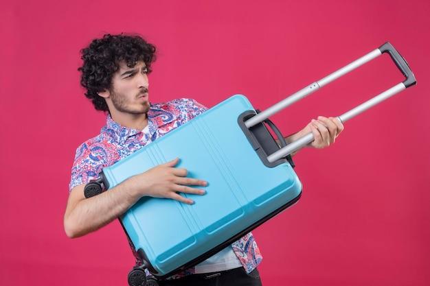 Giocoso giovane viaggiatore riccio bello uomo che tiene la valigia e usandola come chitarra su uno spazio rosa isolato
