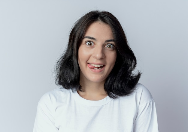 Игривая молодая красивая кавказская девушка показывает язык на белом фоне