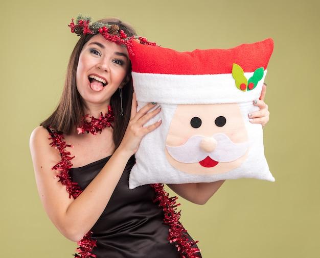 クリスマスの頭の花輪と首の周りに見掛け倒しのガーランドを身に着けている遊び心のある若いかわいい白人の女の子は、オリーブグリーンの背景に分離された舌を示すカメラを見てサンタクロースの枕を保持しています