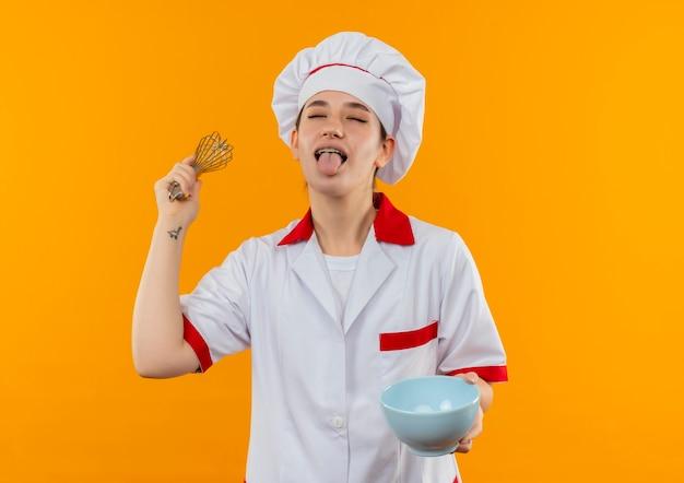 オレンジ色のスペースで隔離された目を閉じて舌を示す泡立て器とボウルを保持しているシェフの制服を着た遊び心のある若いかわいい料理人