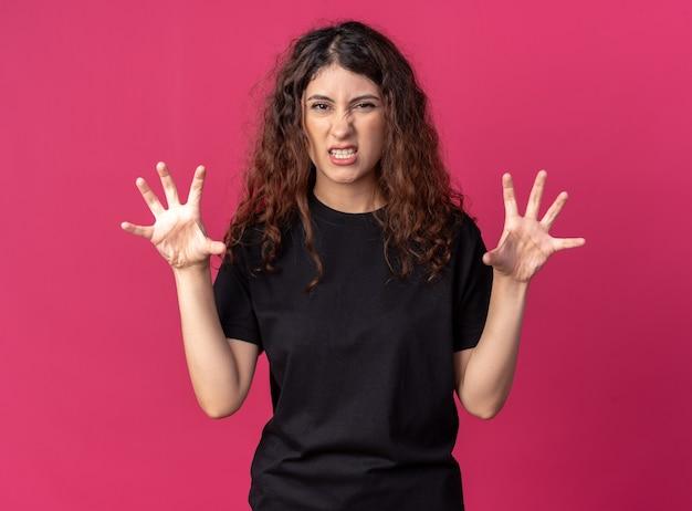 호랑이 포효를 하는 장난기 많은 예쁜 소녀와 진홍색 벽에 격리된 발 제스처