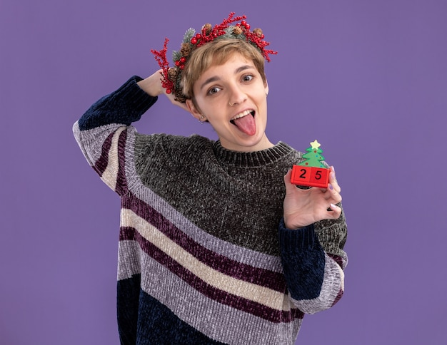 紫色の背景に分離された舌を示す頭の後ろに手を保持しているカメラを見て日付とクリスマスツリーのおもちゃを保持しているクリスマスの頭の花輪を身に着けている遊び心のある若いかわいい女の子