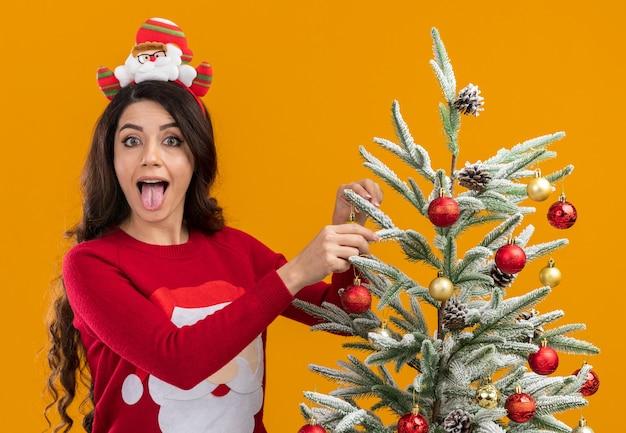 オレンジ色の背景に分離された舌を示すカメラを見てそれを飾るクリスマスツリーの近くに立っているサンタクロースのヘッドバンドとセーターを着て遊び心のある若いかわいい女の子