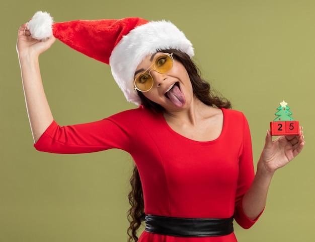 サンタの帽子とメガネを身に着けている遊び心のある若いかわいい女の子は、オリーブグリーンの壁に分離された舌を示す日付をつかむ帽子とクリスマスツリーのおもちゃを保持しています