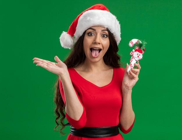 緑の背景に分離された空の手と舌を示すカメラを見てキャンディケインの飾りを保持しているサンタの帽子をかぶって遊び心のある若いかわいい女の子