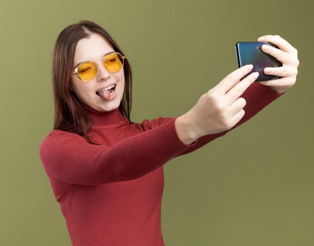 Игривая молодая красивая девушка в солнцезащитных очках показывает язык, делающий селфи