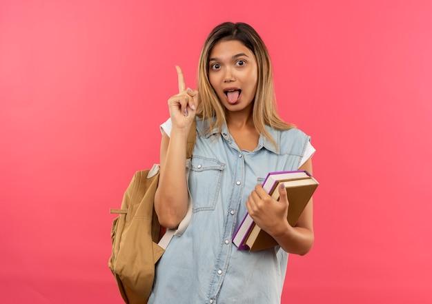 책을 들고 책을 들고 다시 가방을 입고 장난 젊은 예쁜 학생 소녀 복사 공간이 분홍색 배경에 고립 된 혀를 보여주는