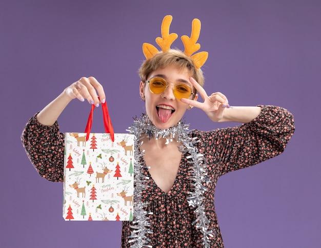 Игривая молодая симпатичная женщина в головной повязке с оленьими рогами и гирляндой из мишуры на шее в очках держит рождественский подарочный пакет