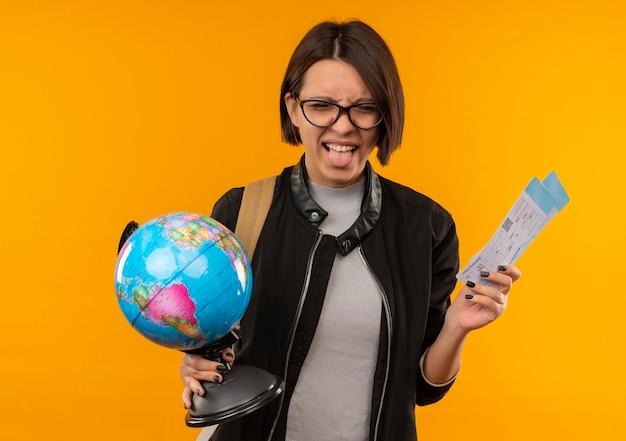 Giocoso giovane studente ragazza con gli occhiali e borsa posteriore in possesso di biglietti aerei e globo che mostra la linguetta isolato su sfondo arancione