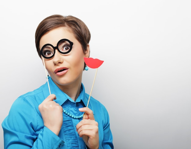 Игривая молодая женщина держит губы и очки на палке