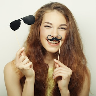 Игривая молодая женщина, держащая усы и очки на палке