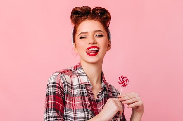 キャンディーでポーズをとる市松模様のシャツを着た遊び心のある若い女性。ロリポップとピンクのスペースに立っている見事なピンナップガール。