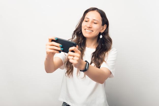遊び心のある若い女性は、彼女が持っている電話で遊んでいます。