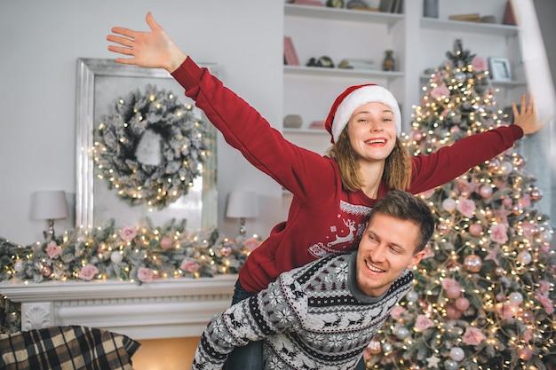 遊び心のある若い女性が男の背中の上に横たわると体の脇に手を繋いでいます。モデルの頭には赤い帽子があります。彼は彼女を保持し、左に見えます。