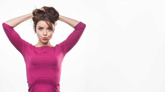 Giovane donna allegra che fa il broncio con le sue mani in testa
