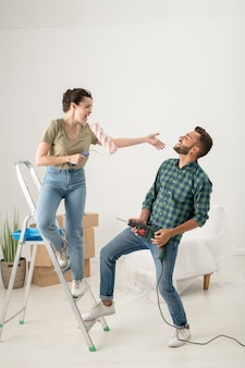 Playful young woman singing into paint roller while her husband using drill as guitar, they having fun while doing renovation