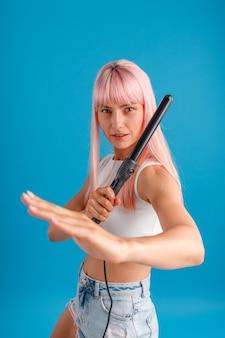 Игривая молодая женщина с розовыми волосами смотрит в камеру, делая позу боевых искусств и держа керлинг
