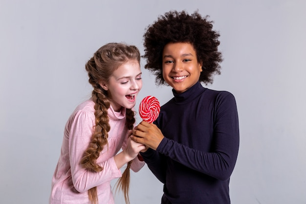 Playfully fighting. cheerful african american boy playing with long-haired friend while working on studio