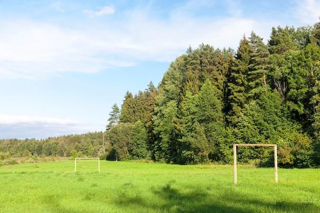 Детская площадка за городом, предназначена для тренировок и игры в футбол. территория леса. на фото крупным планом видны ворота из бревна.
