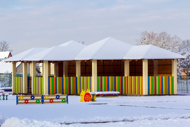 Playground in kindergarten in winter with snow covered swings