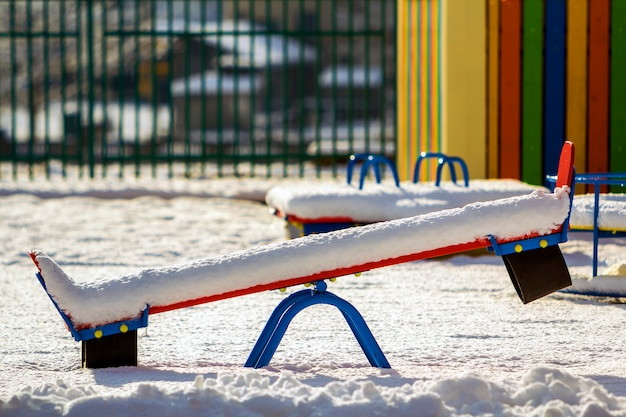 Playground in kindergarten with snow-covered swings