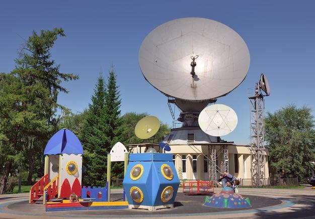青空の下、市内中心部のパラボラアンテナを背景にした遊び場
