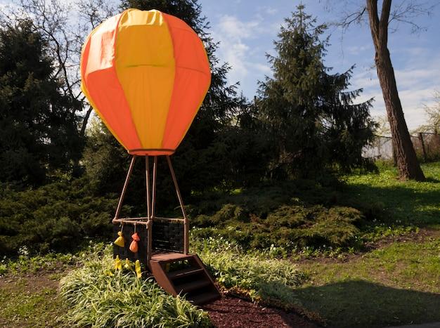 놀이 공간의 공원에서 주황색 노란색 어린이 풍선이 바구니와 함께 놀이터