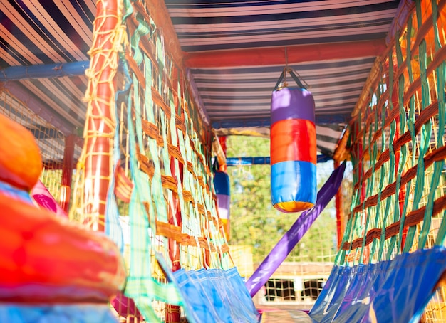 Игровая площадка с красочными ковриками и мягкими предметами для игр, а также большая боксерская груша.