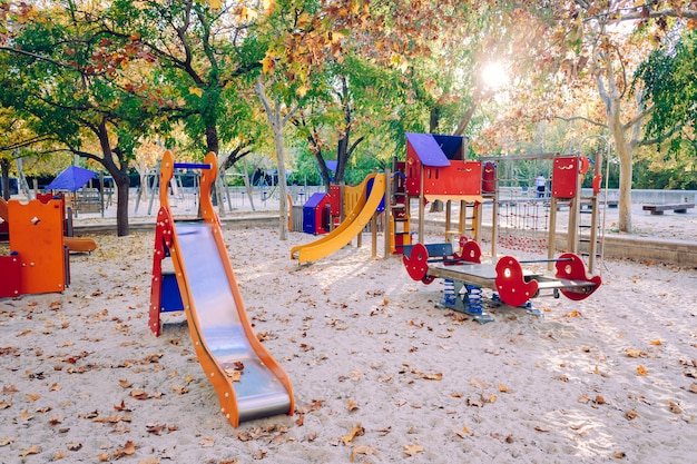 Playground with sand surrounded by trees in the city