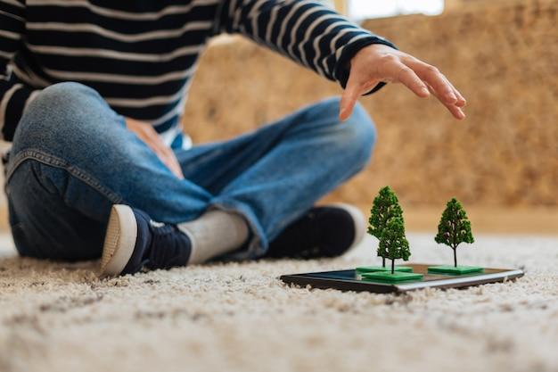 게임하고있는 중. 캐주얼 한 옷을 입고 바닥에 앉아 태블릿에 나무 미니어처를 가진 잘 만들어진 세련된 청년