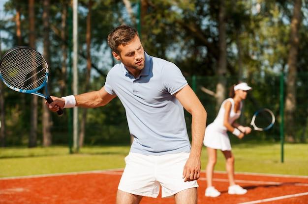 한 팀으로 플레이합니다. 테니스 라켓을 들고 테니스 코트에 서서 여자와 함께 뒤를 바라보는 잘생긴 청년