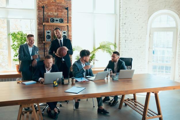 Играет в баскетбол возле рабочего места. счастливые беззаботные коллеги веселятся в офисе, в то время как их коллеги усердно и сосредоточенно работают. понятие о развлечениях, отдыхе, профессиональном занятии.
