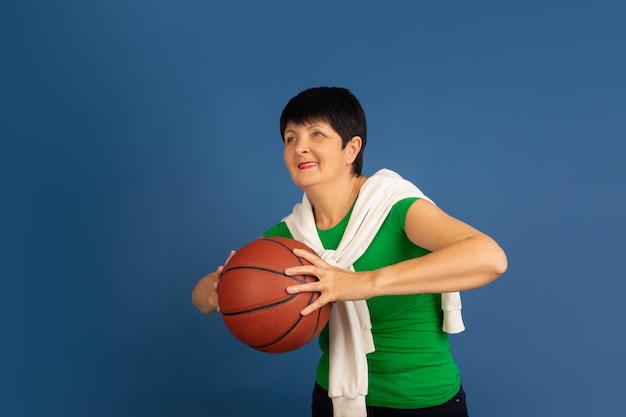 Playing basketball. portrait of senior woman in stylish outfit isolated on blue studio background. tech and joyful elderly lifestyle concept. trendy colors, forever youth. copyspace for ad.