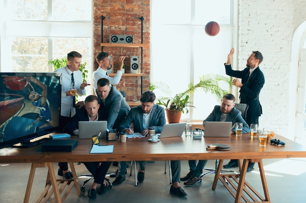 Играл в баскетбол, кричал, смеялся. счастливые беззаботные коллеги веселятся в офисе, в то время как их коллеги усердно и сосредоточенно работают. понятие о развлечениях, отдыхе, профессиональном занятии.