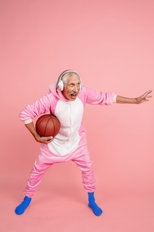 Playing basketball with headphones portrait of senior hipster man in stylish attire